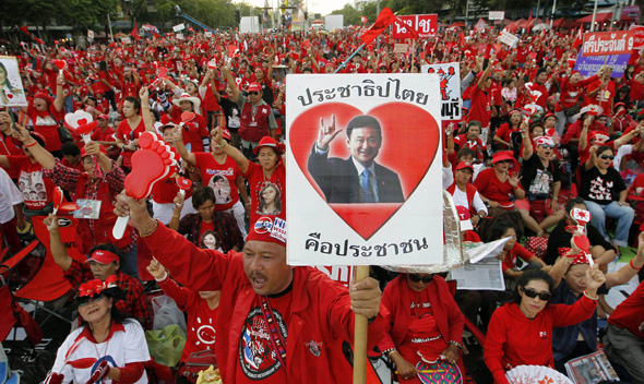 Thailand's red shirt protester holds pictures of former Prime Minister Thaksin Shinawatra during a rally at the Democracy Monument in Bangkok September 18, 2011.