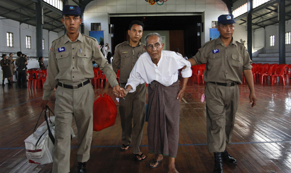 Police assist a newly released prisoner in the meeting hall of Insein Prison in Yangon.