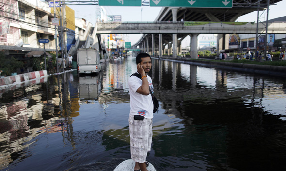 A man stands on sandbags at a flooded intersection in Pathum Thani province, a suburb of Bangkok October 19, 2011.