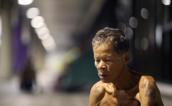 An elderly flood victim sits outside an evacuation centre at an unused airport terminal at Dan Mueang Airport in Bangkok October 24, 2011.