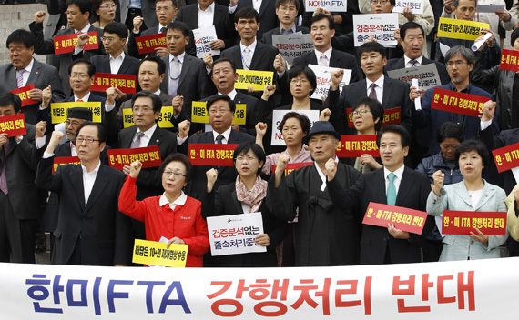 Lawmakers from opposition parties and civic group members chant slogans during a rally opposing the U.S.-South Korea Free Trade agreement (FTA) talks at the National Assembly in Seoul October 12, 2011.