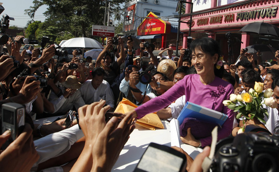 Myanmar democracy leader Aung San Suu Kyi shakes hands with people outside the National League for Democracy (NLD) head office after a meeting in Yangon November 18, 2011.