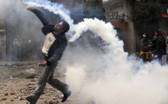 A protester throws a tear gas canister, which had earlier been thrown by riot police, near Tahrir Square in Cairo November 20, 2011.