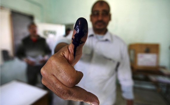 A man shows his ink stained finger after casting his vote at a polling station during parliamentary elections in Cairo November 28, 2011.