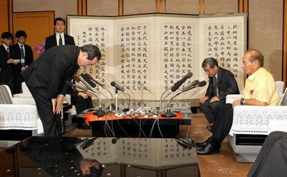 Defense Minister Yasuo Ichikawa, left, apologizes to Okinawa Governor Hirokazu Nakaima December 2, 2011 (Tadashi Mizowaki/Courtesy to the Asahi Shimbun)