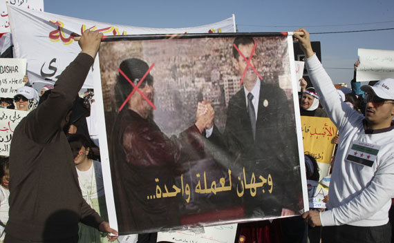 Syrian protesters hold a poster which shows Bashar al-Assad and Muammar Gaddafi during a protest calling for al-Assad to step down in Amman on May 1, 2011.
