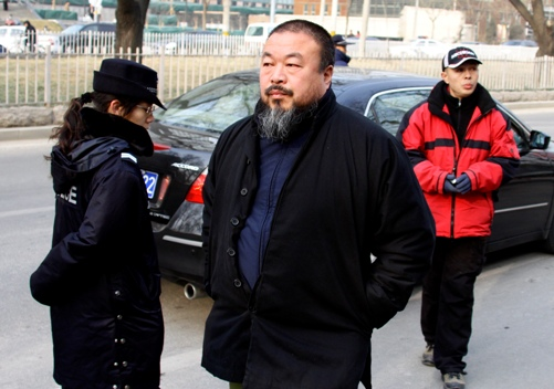 Chinese artist Ai WeiWei (C) walks past police as he arrives to give support to Liu Xiaobo, one of China's most prominent dissidents, outside the courthouse where Liu is on trial in Beijing December 23, 2009. Liu went on trial on subversion charges on Wednesday, drawing an outcry at home and abroad over the country's sweeping laws against political opponents. Chinese prosecutors accuse Liu of