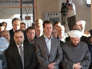 Syria's President Bashar al-Assad prays during the first day of Eid al-Adha at a mosque in the Damascus suburb of Daraya, Syria in this handout picture provided by SANA on September 12, 2016. (SANA/Reuters).