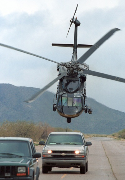 A CBP Blackhawk helicopter intimidates two vehicles on a remote air strip in the southwest border region of the United States (James Tourtellotte/Courtesy Customs and Border Patrol).