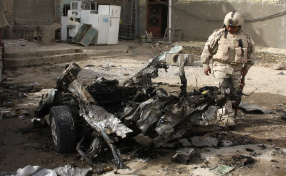 A soldier inspects the remains of a vehicle used in a bomb attack in Baghdad's Sadr city on May 22, 2011 (Kareem Raheem/Courtesy Reuters).