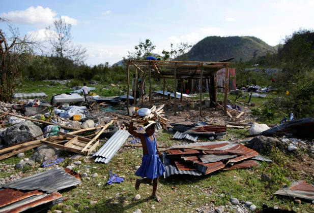 An adolescent girl carrying wood walks near debris after Hurricane Matthew passed, in Camp Perrin, Haiti, October 8, 2016. REUTERS/Andres Martinez Casares
