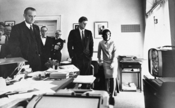 President John F. Kennedy, First Lady Jacqueline Kennedy, McGeorge Bundy, and other advisors gather around a television.