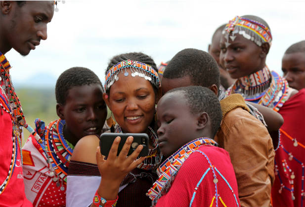 Maasai girls watch a video on a mobile phone prior to the start of an event advocating against harmful traditional practices in Imbirikani, Kenya, April 21, 2016. In Kenya, as in many countries around the world, national statistical systems have been ill-equipped and under-funded to collect data on ethnic minorities, rural communities, and indigenous populations. REUTERS/Siegfried Modola
