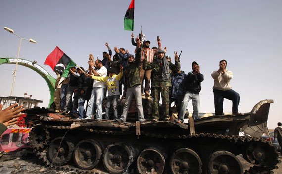 People celebrate atop a destroyed tank belonging to forces loyal to Qaddafi after an air strike by coalition forces in Ajdabiyah.