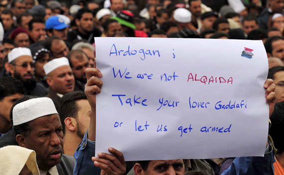 Man holds a sign during prayers in Benghazi on April 1, 2011.