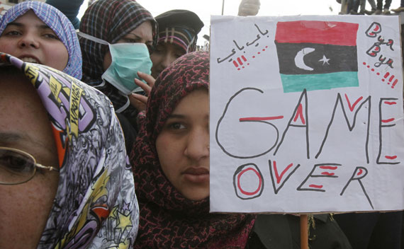 An anti-government protester holds a banner while protesters chant anti-government slogans in Benghazi city