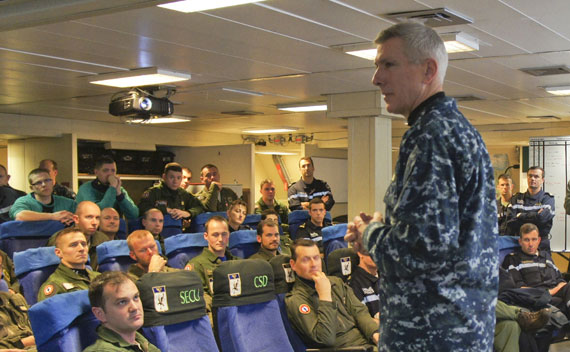 U.S. Admiral Locklear speaks with an aircrew from the French Navy aircraft carrier Charles de Gaulle operating in Mediterranean Sea on March 21, 2011.