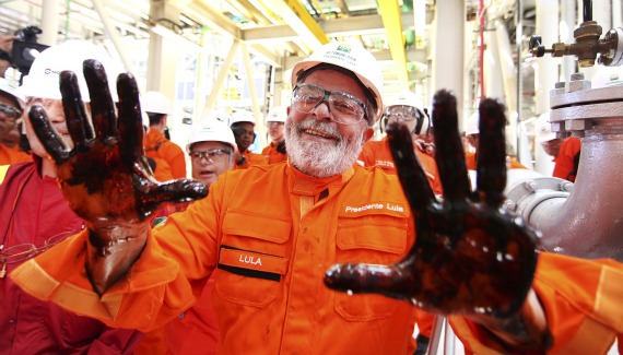 Brazil's President Luiz Inacio Lula da Silva holds up his oil-covered hands at the Cidade Angra dos Reis offshore platform.