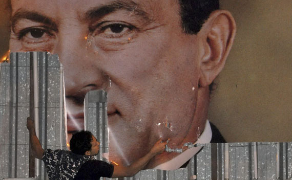 An anti-government protester defaces a picture of Egypt's President Hosni Mubarak in Alexandria.