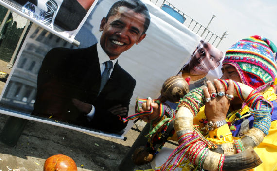 A shaman performs a ritual in front of a photograph of President Barack Obama in Lima.