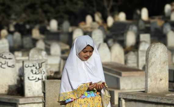 A girl prays near graves on Eid al-Fitr at a cemetery in Ramallah on August 30, 2011 (Mohamad Torokman/Courtesy Reuters).