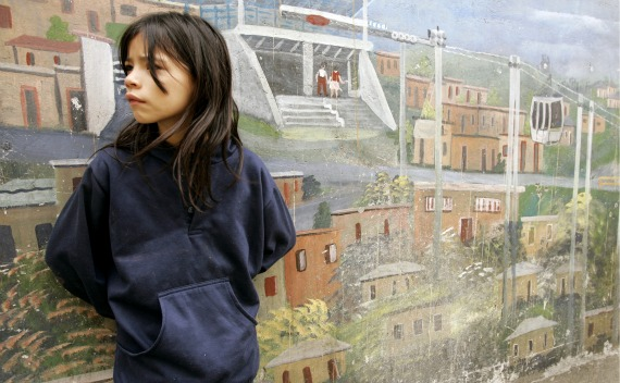 A girl stands in front of a mural as she waits for Spain's King Juan Carlos and Queen Sofia for the inauguration of a public library in a suburb of Medellin (Jose Gomez/Courtesy Reuters).