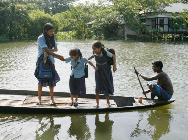 Girls are transported to school by boat in Srinagar, Bangladesh (Courtesy Reuters/Rafiqur Rahman).