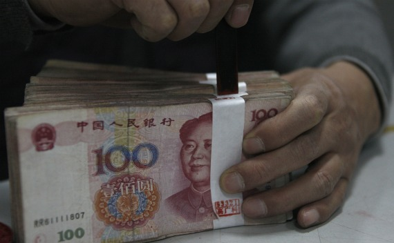 An employee seals a stack of yuan banknotes at a branch of Industrial and Commercial Bank of China in Huaibei, Anhui province on April 6, 2011.