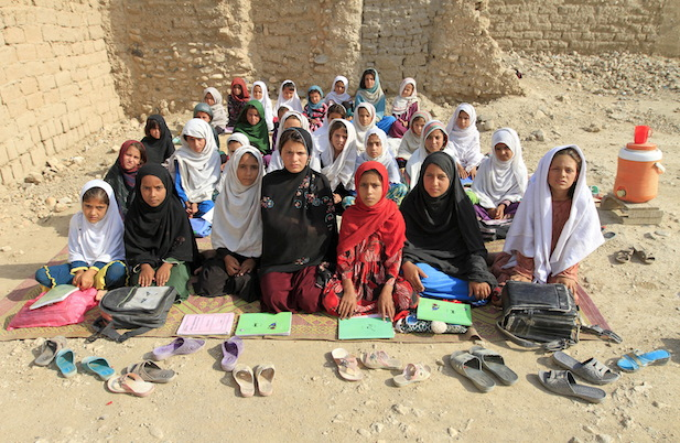 Teacher Mahajera Armani and her class of girls pose for a picture at their study open area, founded by Bangladesh Rural Advancement Committee (BRAC), outside Jalalabad city, Afghanistan September 19, 2015. Nearly three years after Taliban gunmen shot Pakistani schoolgirl Malala Yousafzai, the teenage activist last week urged world leaders gathered in New York to help millions more children go to school. World Teachers' Day falls on 5 October, a Unesco initiative highlighting the work of educators struggling to teach children amid intimidation in Pakistan, conflict in Syria or poverty in Vietnam. Even so, there have been some improvements: the number of children not attending primary school has plummeted to an estimated 57 million worldwide in 2015, the U.N. says, down from 100 million 15 years ago. (Courtesy Reuters/Parwiz)