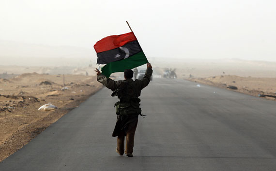 A rebel fighter holds a Kingdom of Libya flag in a battle near Ras Lanuf