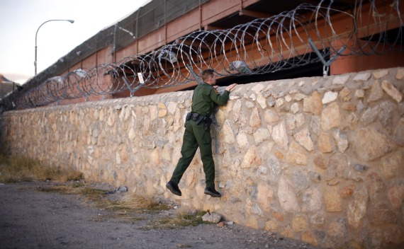 A U.S. Border Patrol agent checks an area under a bridge crossing between the United States and Mexico (Eric Thayer/Courtesy Reuters).