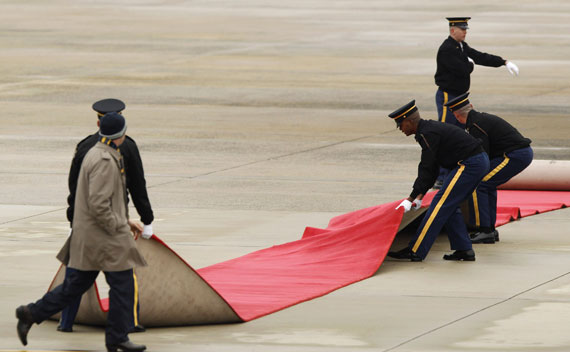 U.S. Air Force personnel adjust the red carpet before the arrival of China's President Hu Jintao at Andrews Air Force Base.
