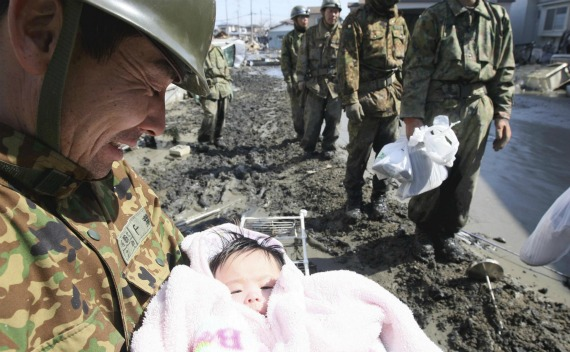 A Japan Self-Defense Forces officer smiles as he holds a four-month-old baby girl who was rescued along with her family members from their home in Ishimaki City, Miyagi Prefecture in northern Japan, after an earthquake and tsunami struck the area on March 14, 2011.