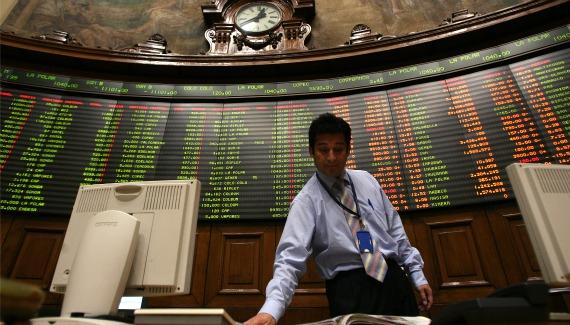 A trader checks a newspaper at the Santiago Stock Exchange (Ivan Alvarado/Courtesy Reuters)