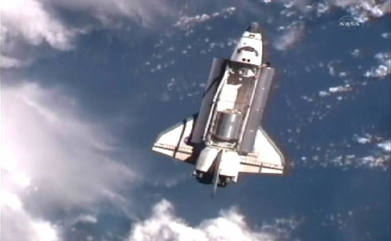 The space shuttle Atlantis is seen with earth in the background as it draws near the International Space Station for docking (Courtesy Reuters).