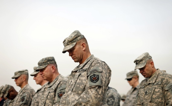 U.S. military personnel lower their heads during the ceremony of the encasing of the U.S. Forces in Iraq colors in Baghdad on December 15, 2011 (Courtesy Reuters/Pool).
