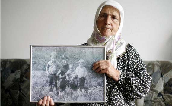 Munira Salihovic poses with picture of her three sons and husband, who were killed during the Srebrenica massacre.