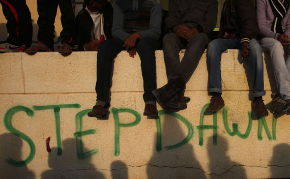 Protesters sits atop a wall during anti-Qaddafi demonstrations on March 14, 2011.