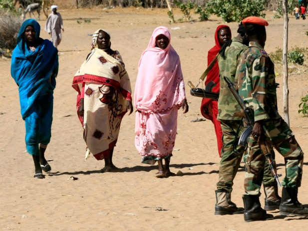 Military personnel walk past women in Tabit village in North Darfur, Sudan. The joint peacekeeping mission in the region known as UNAMID visited Tabit in November 2014 to investigate media reports of an alleged mass rape of 200 women and girls (Courtesy Mohamed Nureldin Abdallah/Reuters).