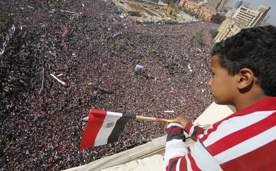 A boy watches as pro-democracy supporters gather in Tahrir Square in Cairo on February 18, 2011.