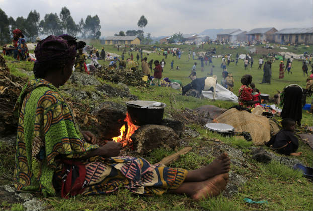 A woman displaced by fighting between the Congolese army and M23 rebels in eastern Democratic Republic of Congo prepares dinner in a field with other displaced families. (James Akena/Reuters)