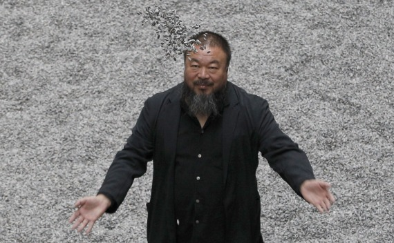 Chinese artist Ai Weiwei throws porcelain sunflower seeds into the air as he poses for a photograph with his installation entitled 'Sunflower Seeds', at its unveiling at the Tate Modern gallery, in London on October 11, 2010.