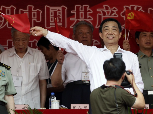 Chongqing Municipality Communist Party Secretary Bo Xilai waves a Chinese national flag during the opening ceremony of a revolutionary song singing concert at Chongqing Olympic Sports Centre in Chongqing municipality on June 29, 2011. More than 70,000 people attended the ceremony to celebrate the 90th anniversary of the founding of the Communist Party of China (CPC) on July 1.