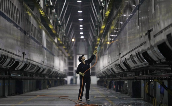 An employee hoses a China Railway High-speed Harmony bullet train at the high-speed train maintenance base in Wuhan, Hubei province on October 19, 2011.