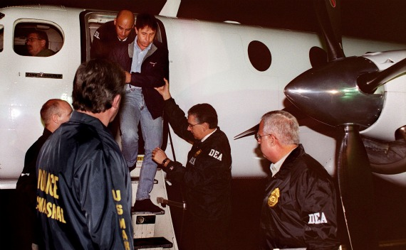 U.S. Drug Enforcement Administration agents usher Fabio Ochoa, Colombian drug kingpin, to an awaiting vehicle following his extradition from Colombia to  Florida, September 8, 2001(Courtesy Reuters).