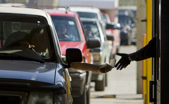 A customs officer is handed a passport by a motorist at the San Ysidro border crossing (Fred Greaves/Courtesy Reuters).