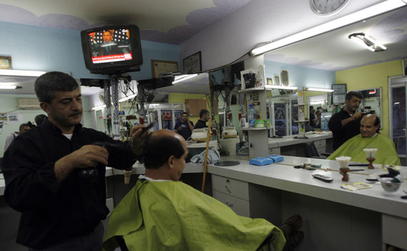 Obama is seen on a television in the background of a barber shop near Ramallah (Mohamad Torokman/Courtesy Reuters)