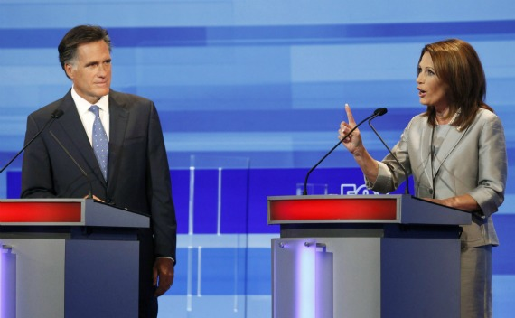 U.S. Republican presidential candidate Michele Bachmann gestures beside Mitt Romney during the Republican presidential debate in Ames (Courtesy Reuters).