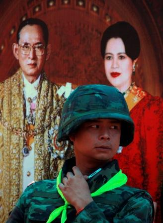 A Thai soldier stands guard near a portrait of Thai King Bhumibol  Adulyadej and Queen Sirikit at a checkpoint in central Bangkok May 21,  2010.