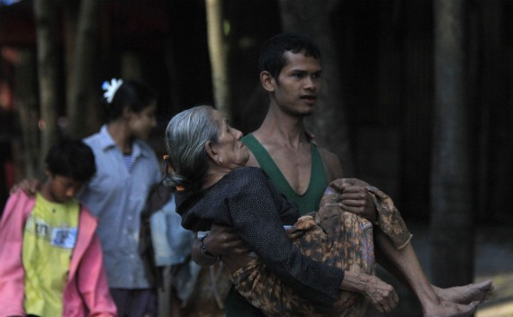 A Myanmar refugee, who crossed over from Myanmar to Thailand when a battle erupted between Myanmar's soldiers and rebels, carries his relative at the Thai border town of Mae Sot on November 8, 2010.